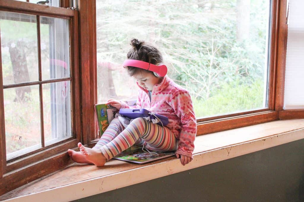 Toddler girl using tablet with headphones