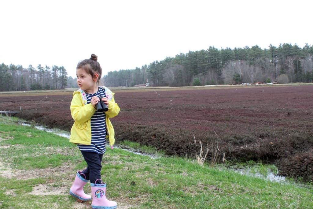 Girl in rain boots plays outside.