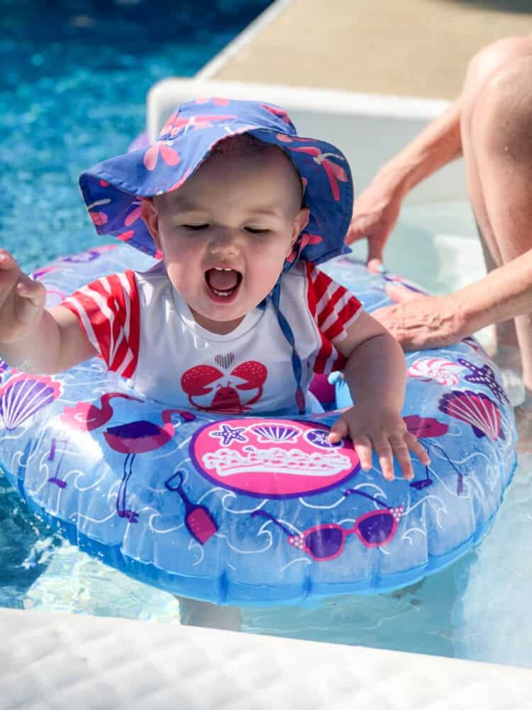 Baby splashing in pool with float