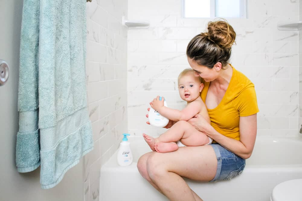 Mom and baby sitting on edge of bathtub with Baby Dove Rich Moisture products