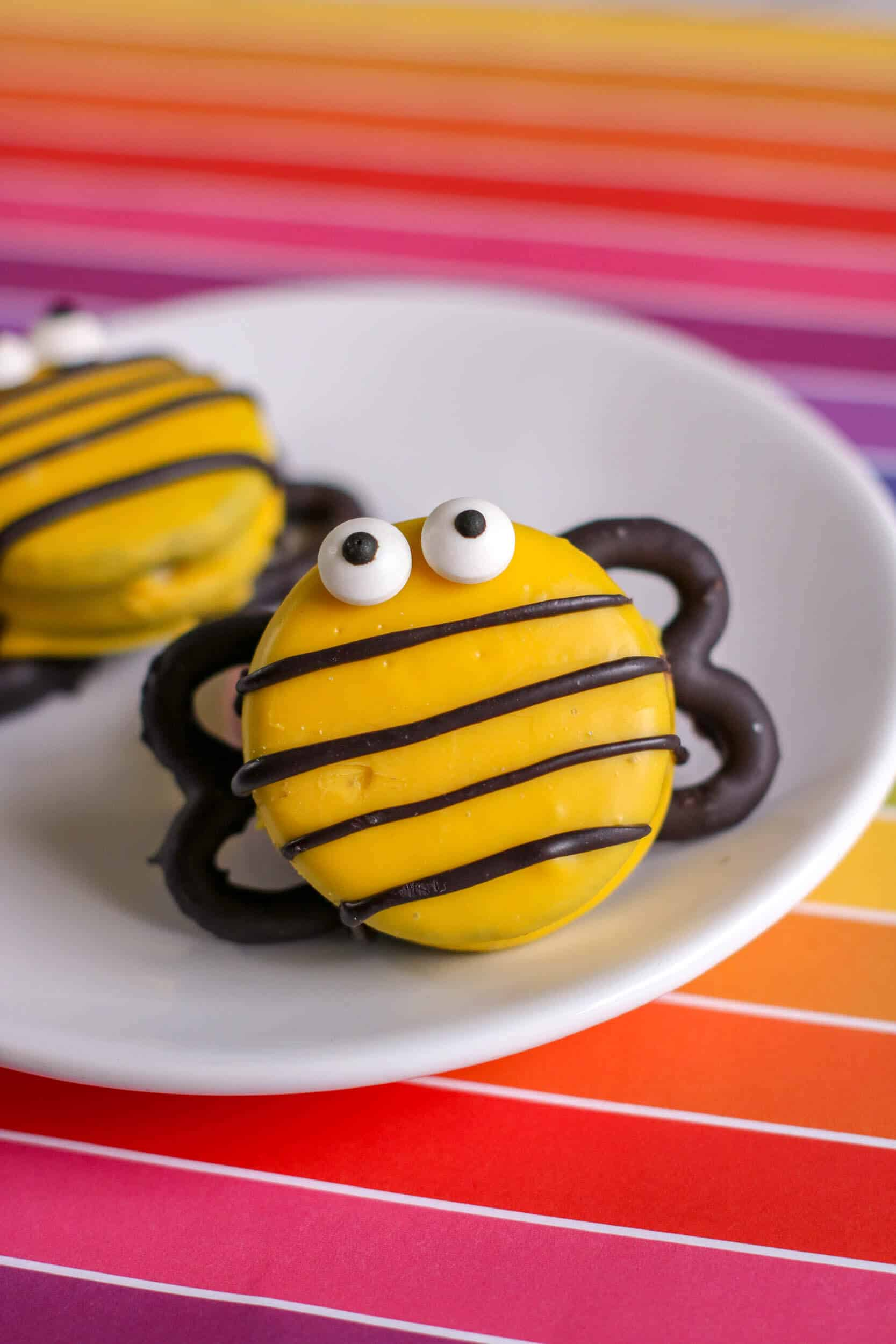 """Decorated cookie \""""bees\"""" on white plate."""