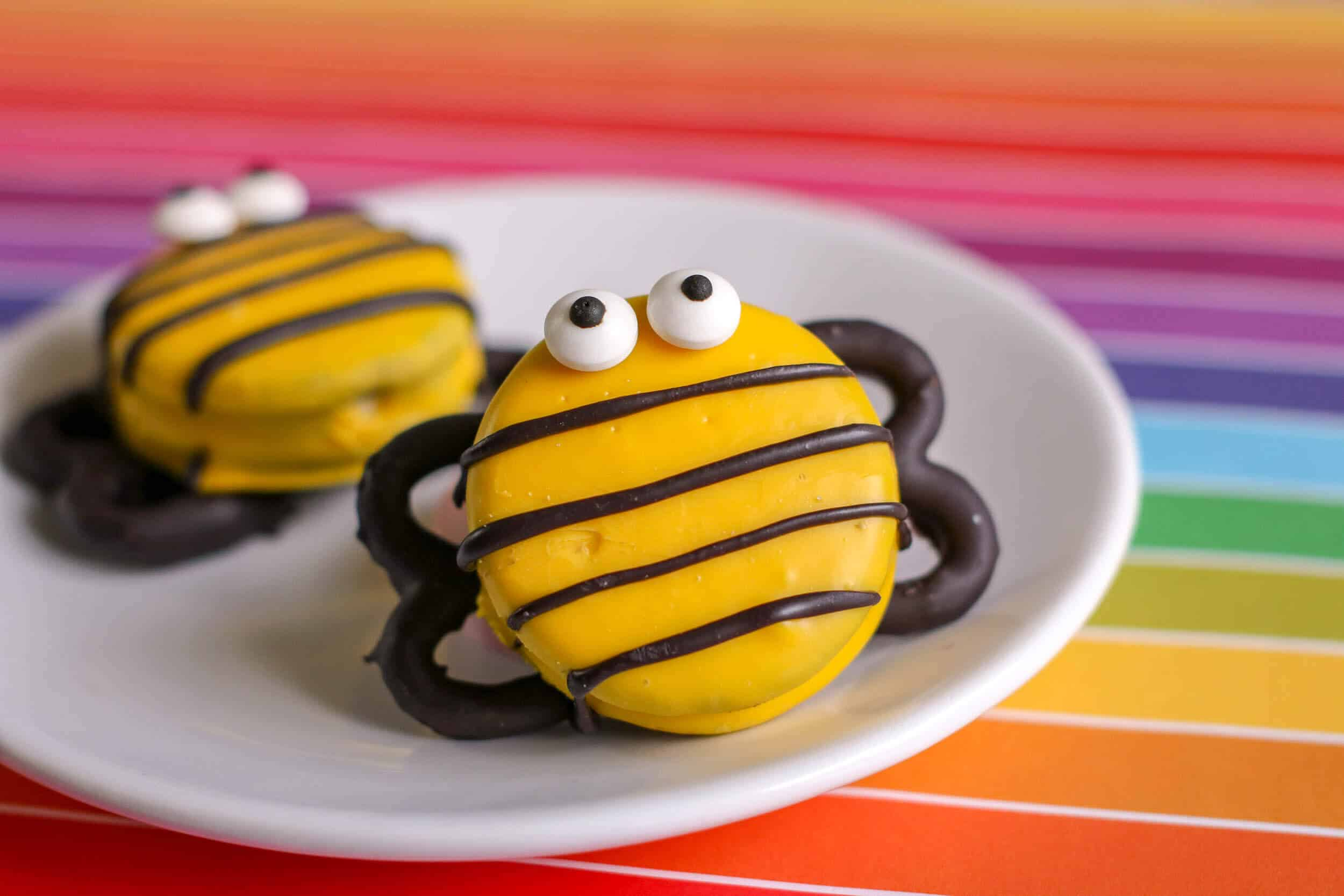 DIY bee decorated cookies on white plate.