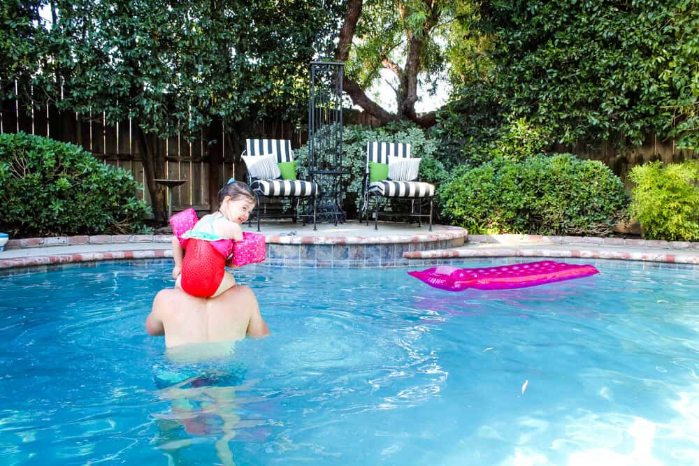 child and adult swimming in pool