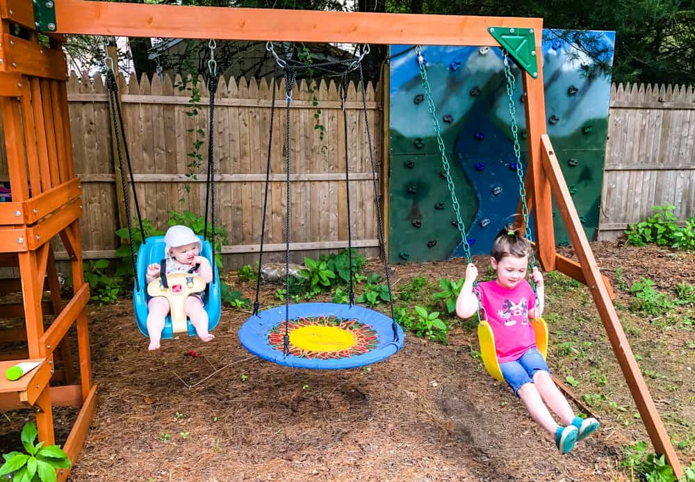 Kids playing on swingset with DIY climbing wall in background