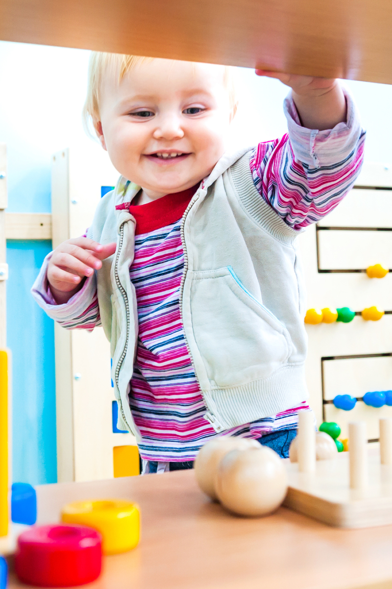 toddler playing with wooden montessori toys