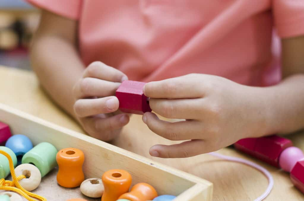 child threading beads in montessori play