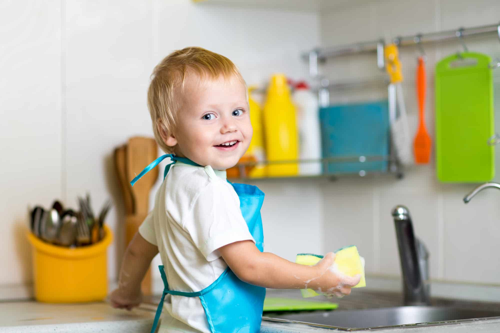 Toddler standing a sink doing montessori practical life activties