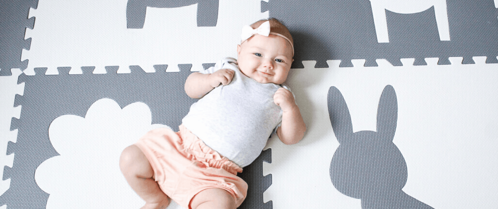 Baby smiling on play mat