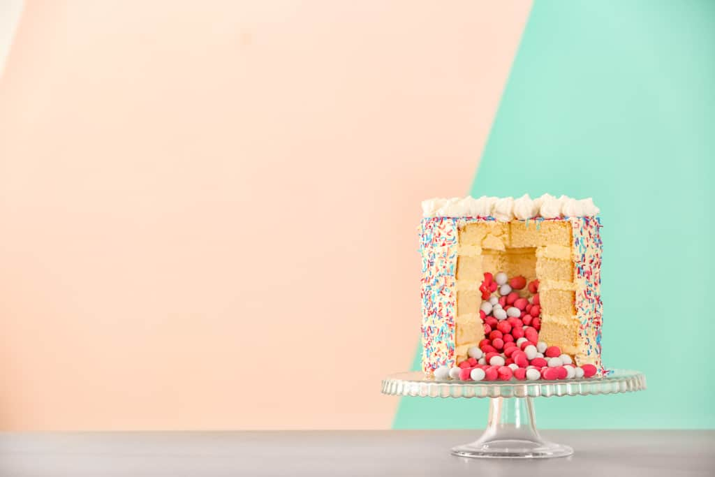 Gender reveal cake against a pink and blue background, easy gender reveal idea