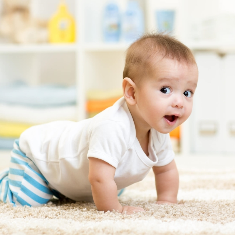 baby crawling in front of montessori toy shelf