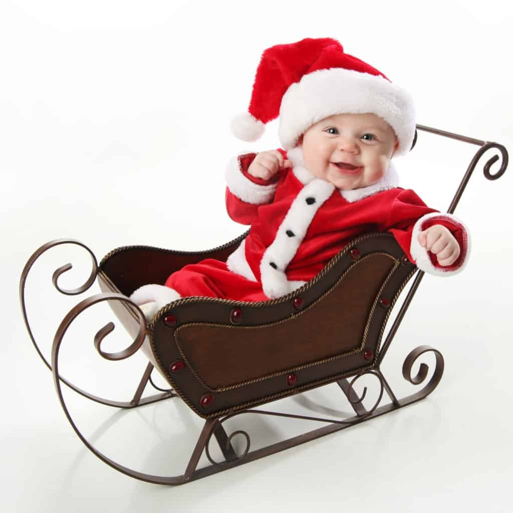 Adorable young baby wearing a santa claus suit and hat sitting in a metal Christmas snow sleigh