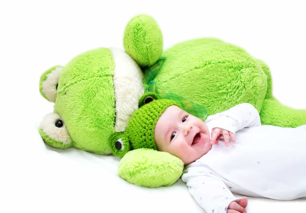 baby in frog hat laying on frog stuffed animal