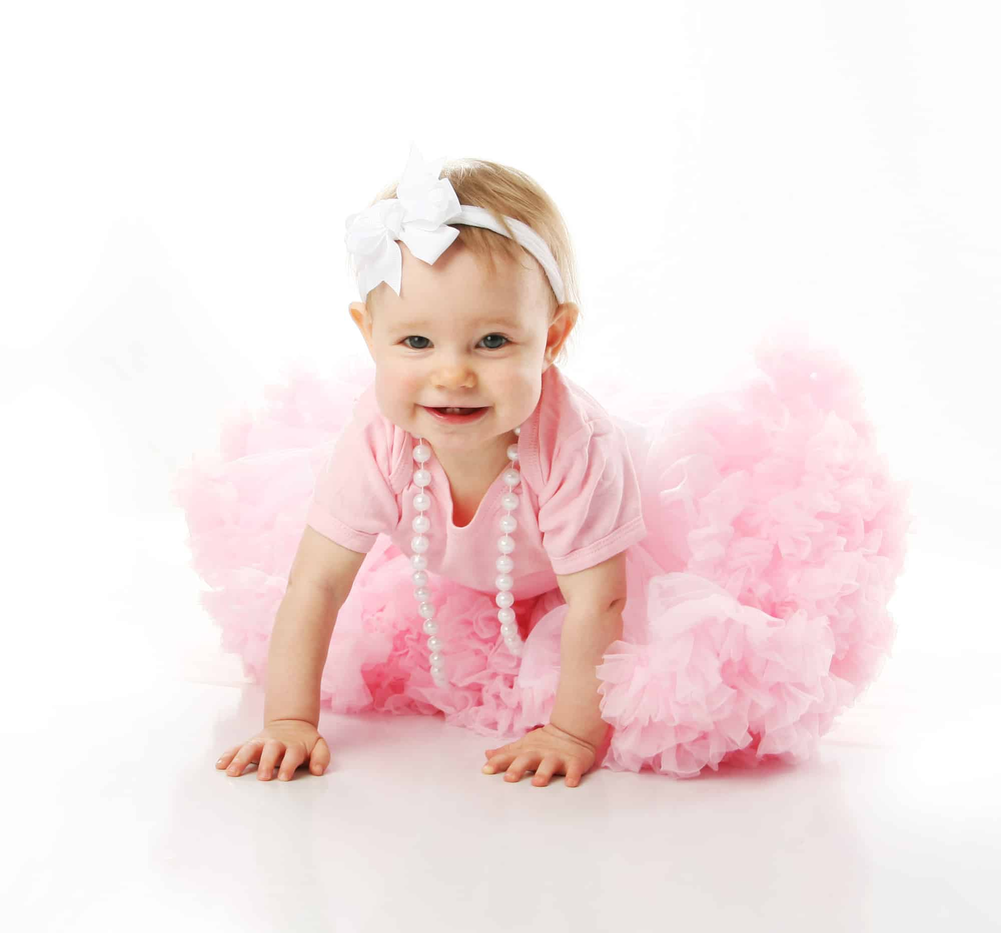 Baby girl crawling while wearing pink tutu