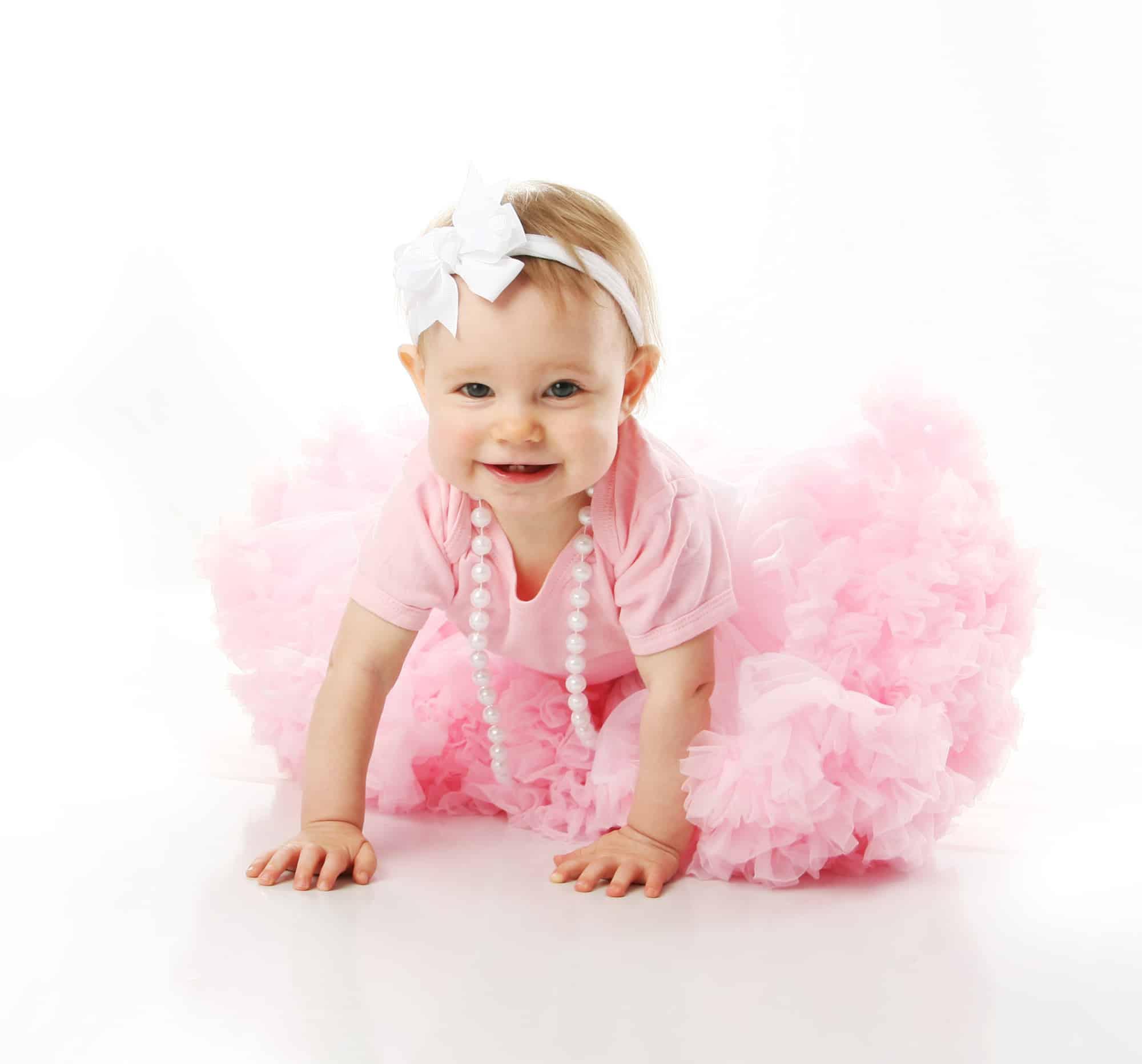 Baby girl crawling while wearing pink tutu