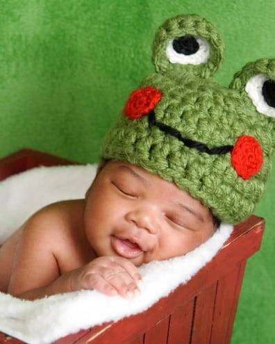 Baby with crochet frog hat lays in blanket lined basket.