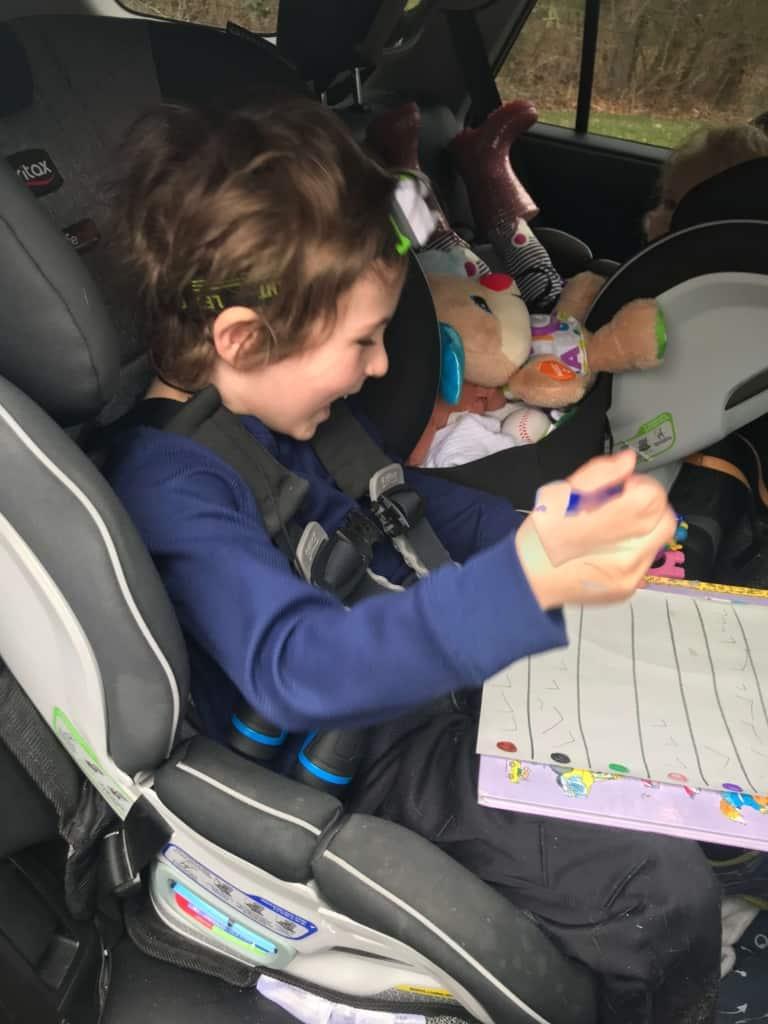 Children in car participate in bear hunt activity.