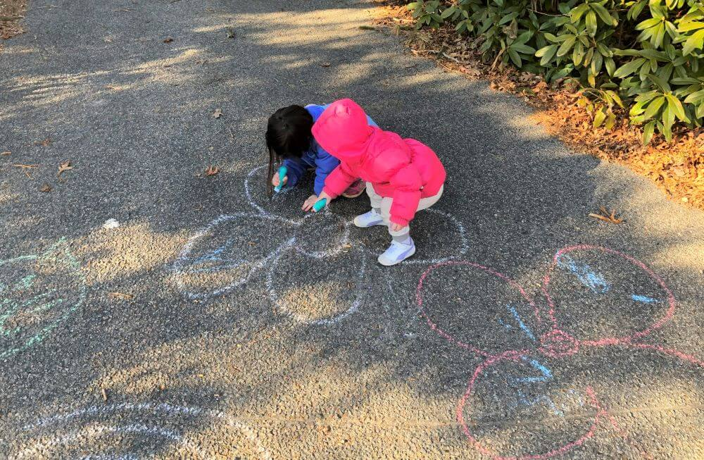 Children use chalk to draw on concrete for a fun birthday activity at home.