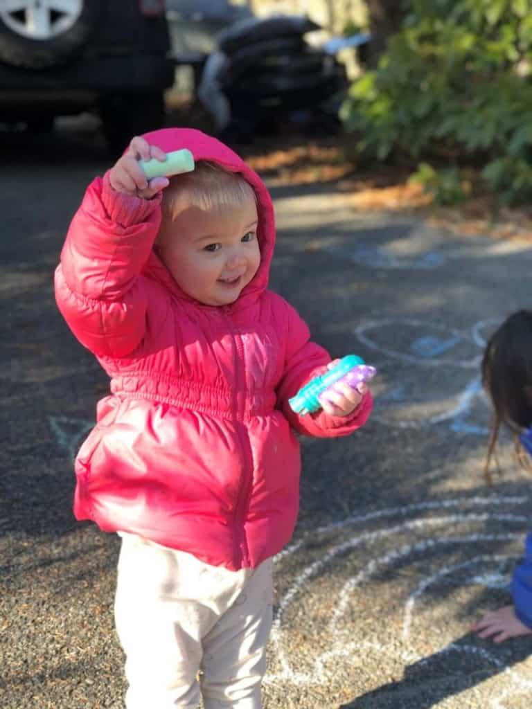 Toddler girl holds sidewalk chalk while celebrating birthday at home.