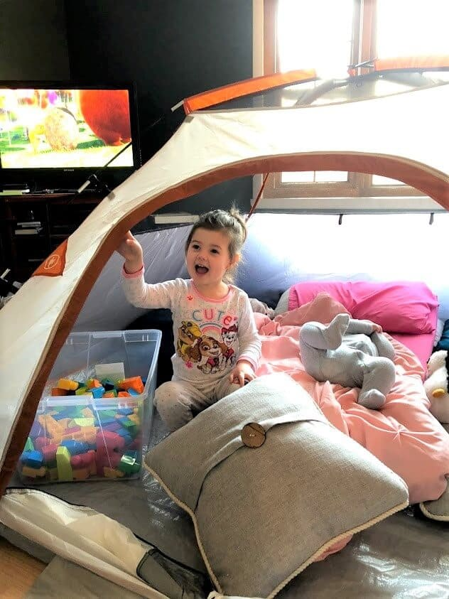 Little girl celebrates birthday at home in tent.