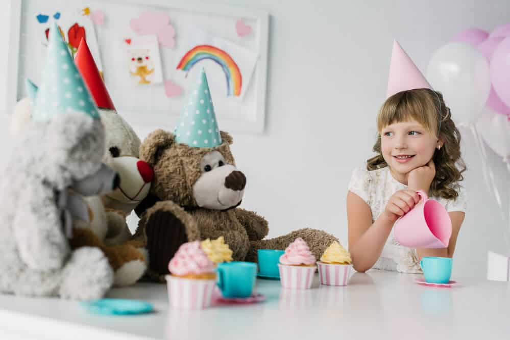 Little girl and her teddy bears wear party hats for her birthday celebration during social isolation.