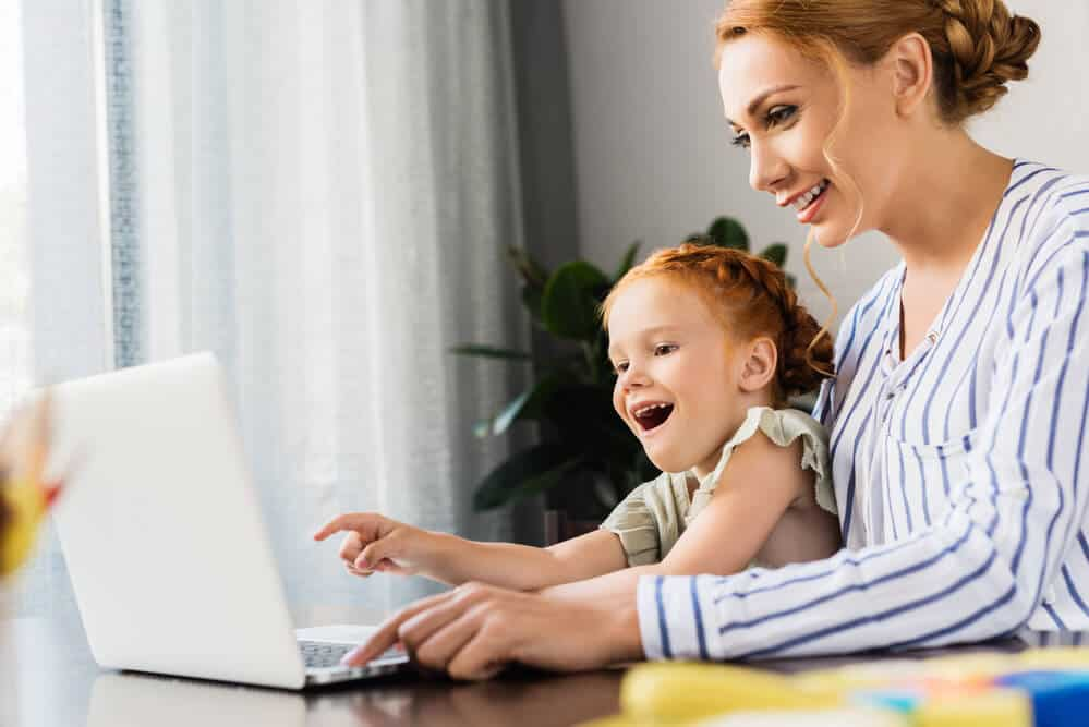 Woman and child use computer for a virtual birthday celebration at home.