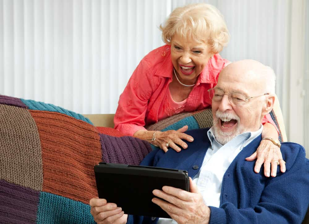Grandparents excited using a tablet.