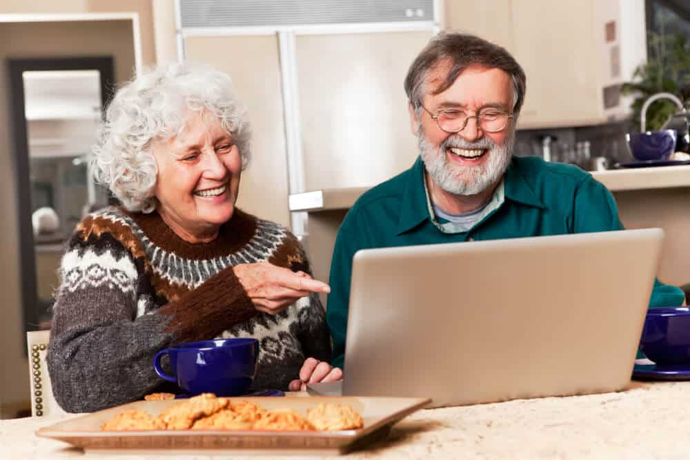grandparents smiling happily at someone during a virtual zoom call on the computer