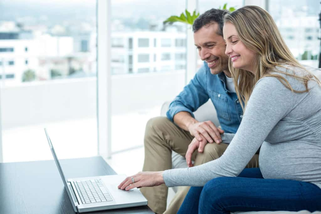 pregnant couple on laptop for virtual gender reveal