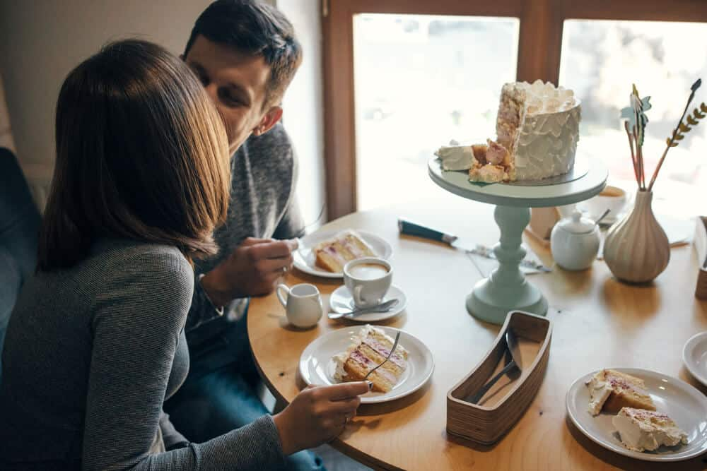 gender reveal cake sliced open with man and woman kissing