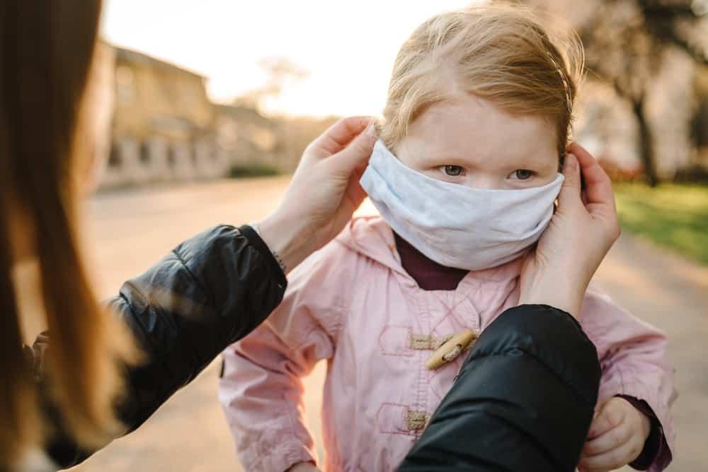 mom putting kids face mask on toddler