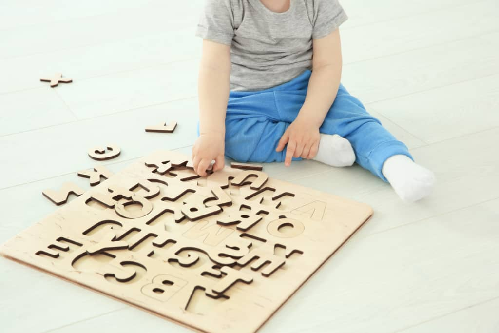 Boy plays with wooden letter puzzle