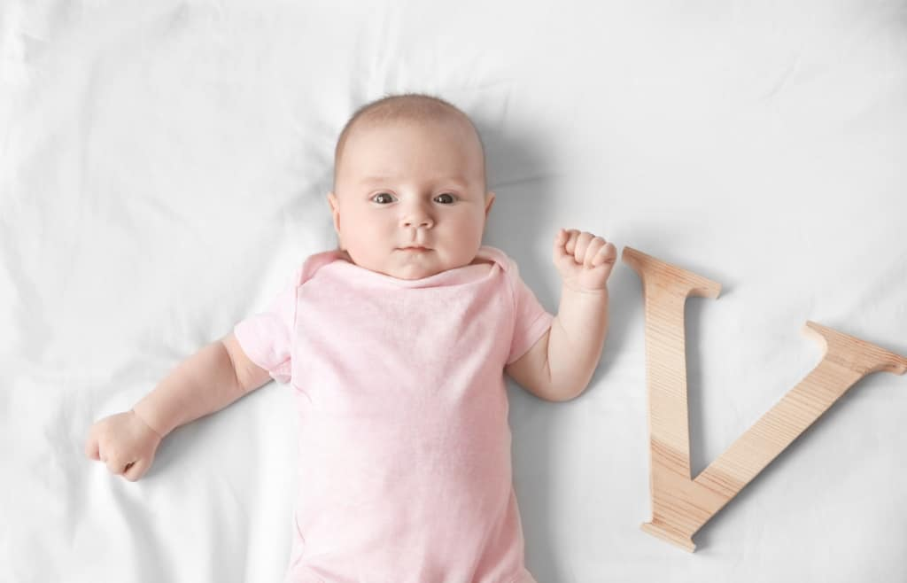 "Baby girl with wooden letter ""V""."