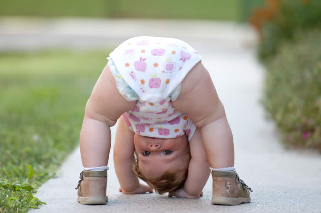 Cute baby girl plays on sidewalk.