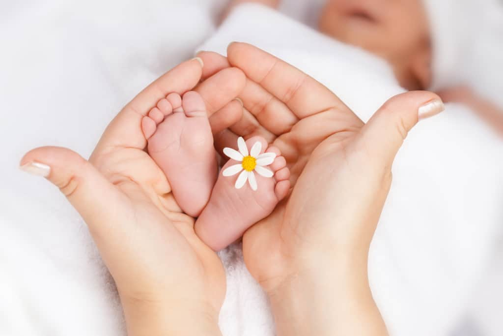 Mother holds baby's feet with flower.