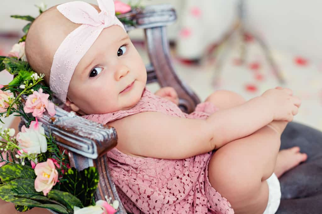 Baby girl reclines in flower covered chair.