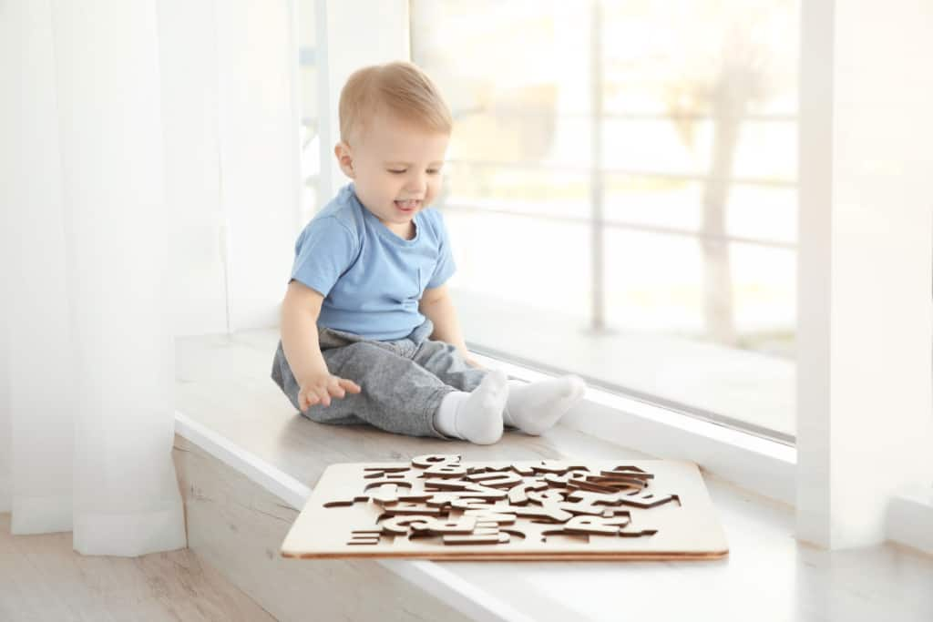 Baby boy plays with wooden letter puzzle.