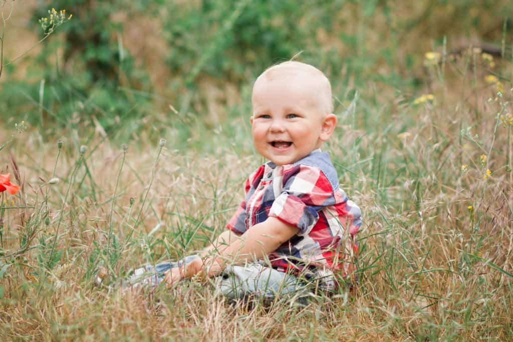 baby boy sitting in nature in grass field