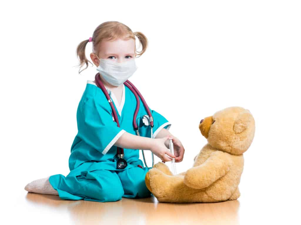 girl child wearing doctor costume with face mask attending to teddy bear