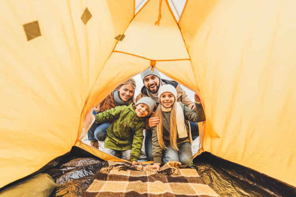 Family poses in tent using the best Fall camping tips for families.