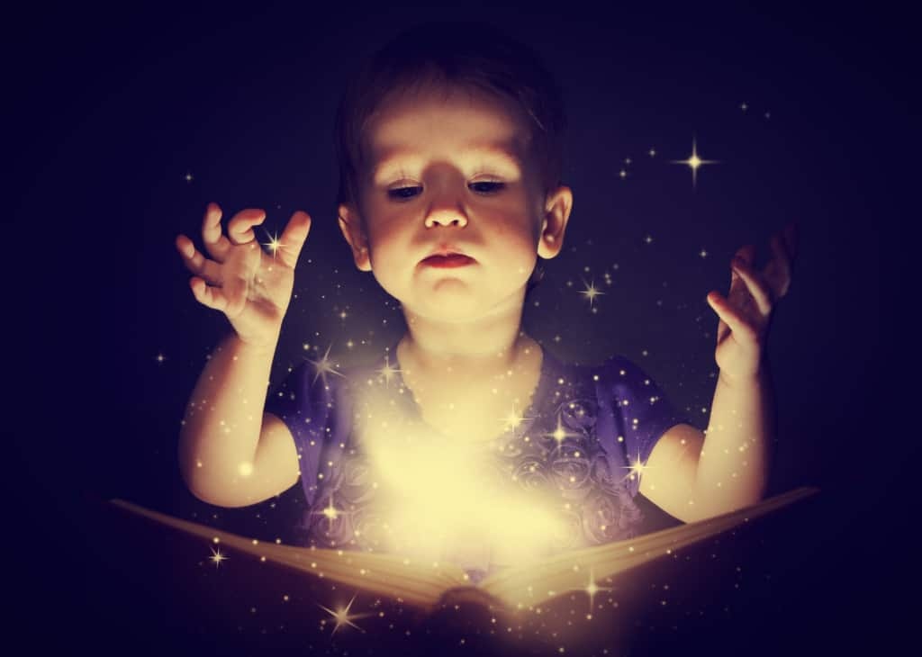 Fairy baby casts spell with magic book.