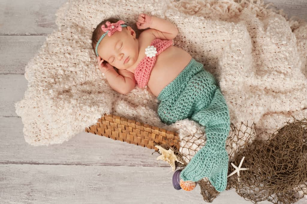 Infant girl in crochet mermaid costume with name from mermaid baby names list.