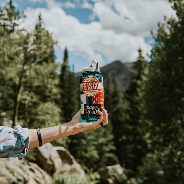 hand holding water bottle outdoors while camping