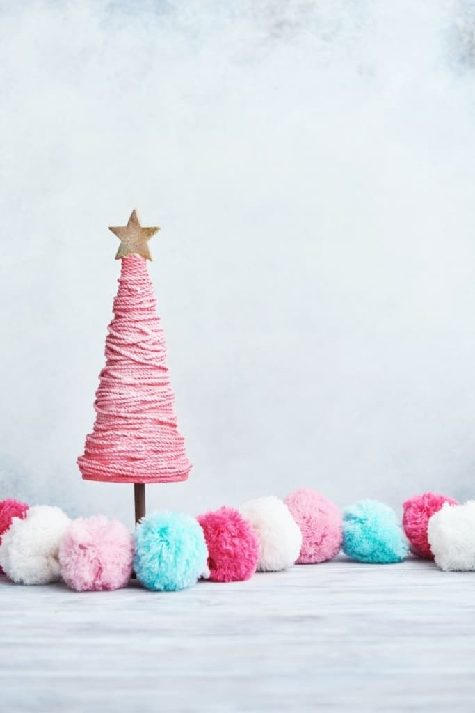 Seasonal gender reveal idea with blue and pink pom poms and mini Christmas tree.