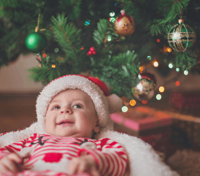 Baby in a basket under the Christmas tree.