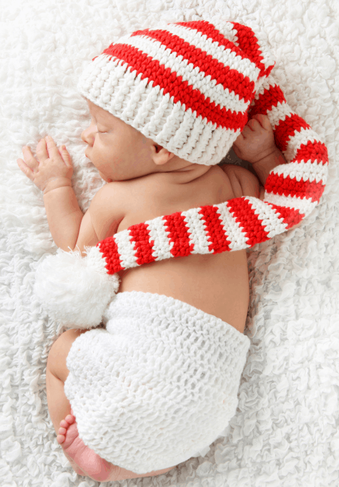 Baby's first Christmas newborn photo with crochet hat.