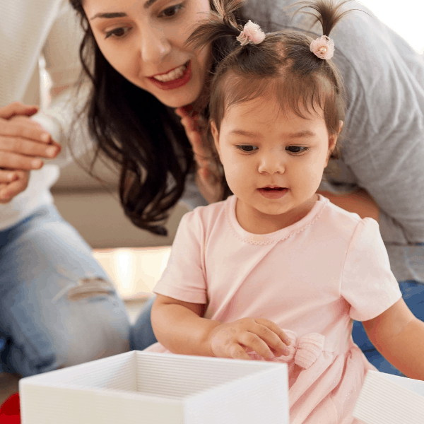1 Year Old girl opens birthday gift with parents.