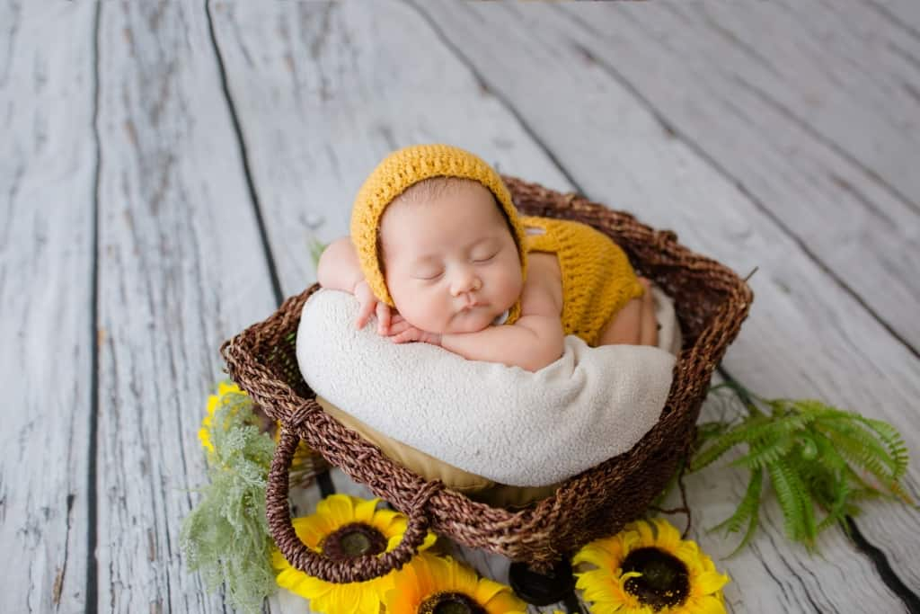 Hippie baby in basket with sunflowers.