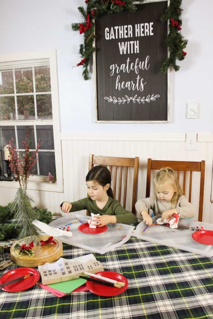 Two girls doing Christmas arts and crafts at a table.