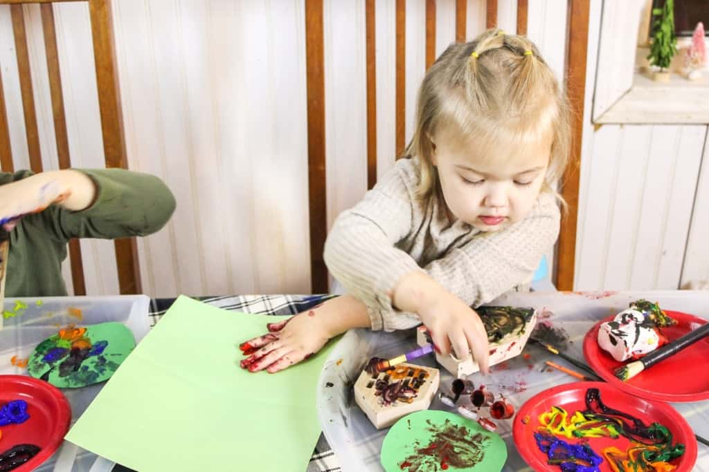 Little girl doing Christmas crafts at a table.