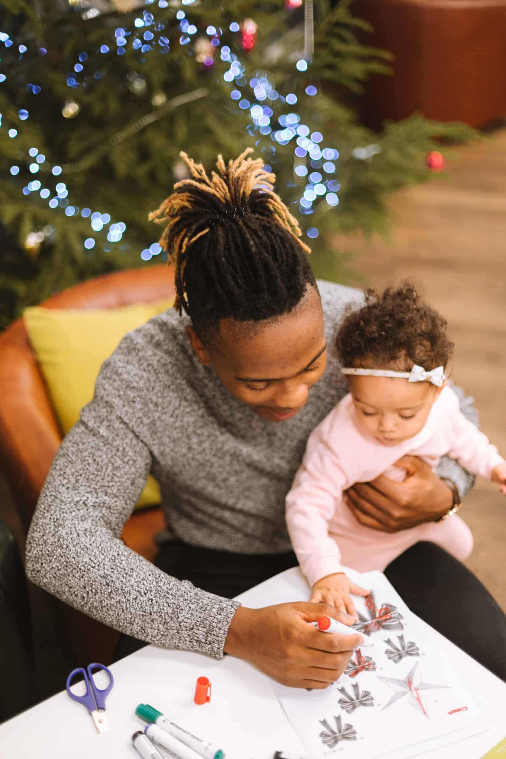 father with daughter coloring for baby's first christmas